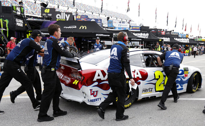 William Byron's crew pushes his car back to the garage after he was involved in a wreck during practice for the NASCAR Cup Series auto race at Daytona International Speedway, Thursday, July 4, 2019, in Daytona Beach, Fla. (AP Photo/Terry Renna)