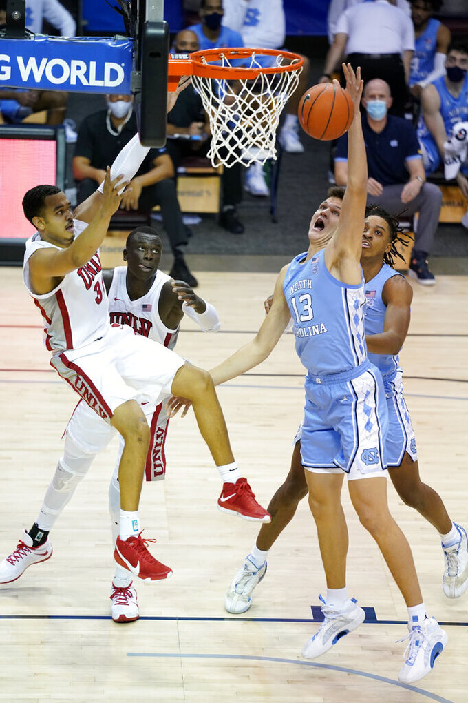 North Carolina forward Walker Kessler (13) reaches for a rebound in front of UNLV forward Devin Tillis (30) in the first half of an NCAA college basketball game in the Maui Invitational tournament, Monday, Nov. 30, 2020, in Asheville, N.C. (AP Photo/Kathy Kmonicek)