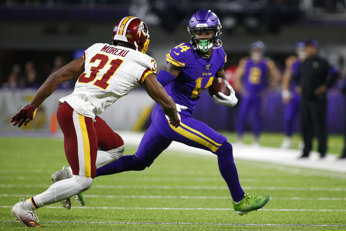 Minnesota Vikings wide receiver Stefon Diggs runs from Washington Redskins cornerback Fabian Moreau, left, after catching a pass during the second half of an NFL football game, Thursday, Oct. 24, 2019, in Minneapolis. (AP Photo/Bruce Kluckhohn)