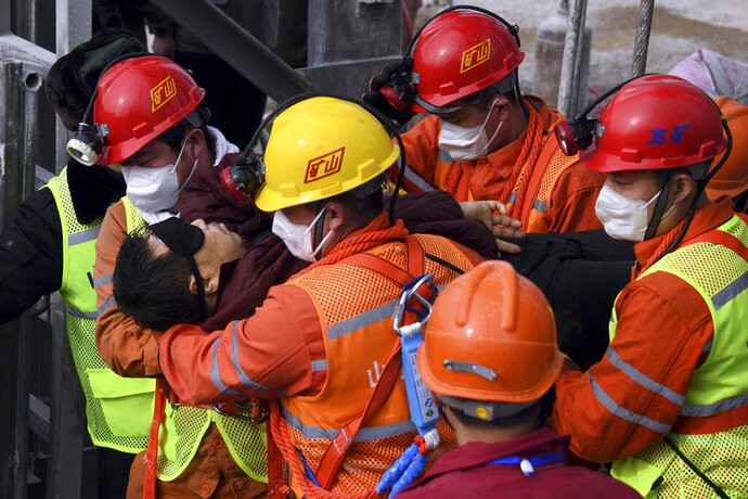 In this photo released by Xinhua News Agency, rescuers carry a miner who was trapped in a mine to an ambulance in Qixia City in east China's Shandong Province, Sunday, Jan. 24, 2021. Eleven workers trapped for two weeks by an explosion inside a Chinese gold mine were brought safely to the surface on Sunday. (Chen Hao/Xinhua via AP)