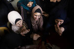 Relatives of Islamic Jihad militant, Abdullah Al-Belbesi, 26, who was killed in Israeli airstrikes, mourn his death in the family home, during his funeral in the town of Beit Lahiya, Northern Gaza Strip, Wednesday, Nov. 13, 2019. Gaza's Health Ministry said Wednesday that more Palestinians have been killed by ongoing Israeli airstrikes, bringing the death toll in the escalation over the past two days to at least 18. (AP Photo/Khalil Hamra)