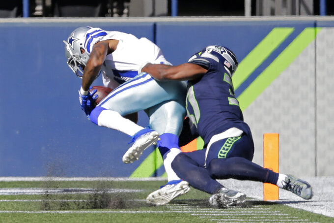 Dallas Cowboys wide receiver Ced Wilson is tackled by Seattle Seahawks free safety Quandre Diggs as Wilson scores a touchdown during the first half of an NFL football game, Sunday, Sept. 27, 2020, in Seattle. (AP Photo/John Froschauer)
