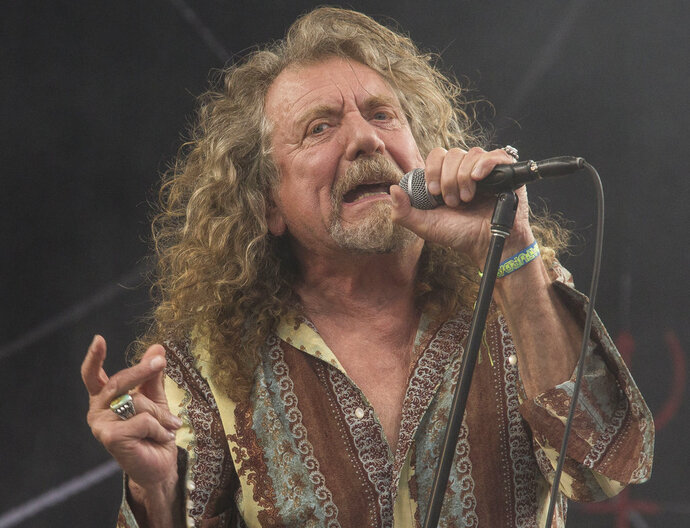 FILE - In this June 28, 2014 file photo, Robert Plant performs on the Pyramid main stage at Glastonbury music festival, in England.  Plant and his backing band, Sensational Space Shifters, made their way to Garland, N.C., after kicking off their U.S. tour in Raleigh on Friday, Feb. 9, 2018.  One top North Carolina eatery kitchen was closed but reassured Led Zeppelin's famished frontman they were going to feed him.   Before their arrival, the owners, James Beard Award-nominated chef Cheetie Kumar and her husband, Paul Siler, who also have a band together, were happy to show the group a whole lotta love.(Photo by Joel Ryan/Invision/AP, File)