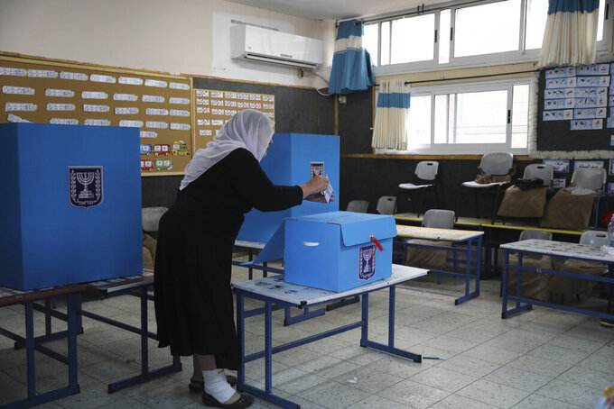 An Israeli Arab woman votes for Israel's parliamentary election at a polling station in Maghar, Israel, Tuesday, March. 23, 2021. Israel is holding its fourth election in less than two years. (AP Photo/Mahmoud Illean)