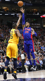 Detroit Pistons' Eric Moreland (24) shoots the ball as Utah Jazz's Derrick Favors (15) defends in the first half of an NBA basketball game on Tuesday, March 13, 2018, in Salt Lake City. (AP Photo/Kim Raff)