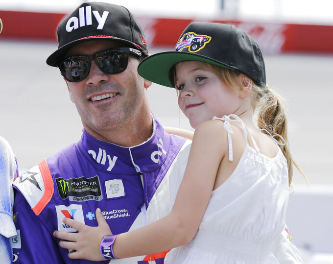 Jimmie Johnson holds his daughter Lydia on pit road before qualifying for the NASCAR Cup series auto race on Saturday, Aug. 31, 2019, at Darlington Raceway in Darlington, S.C.. (AP Photo/Terry Renna)