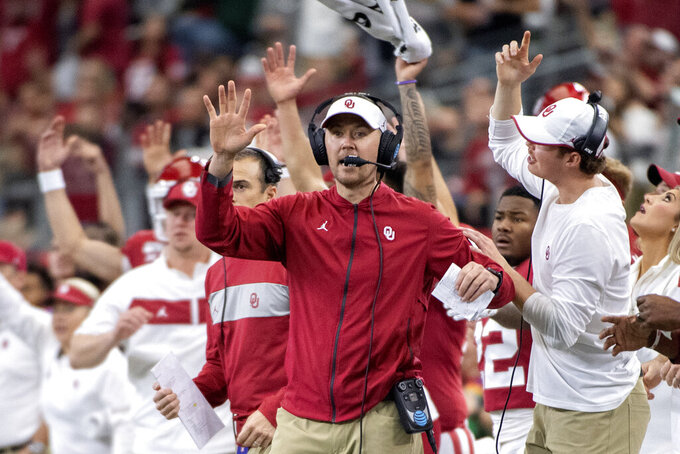 FILE - In this Saturday, Dec. 7, 2019, file photo, Oklahoma head coach Lincoln Riley cheers with his players and coaches during the first half of an NCAA college football game against Baylor for the Big 12 Conference championship, in Arlington, Texas. Riley already has coached Heisman Trophy winners Baker Mayfield and Kyler Murray along with Heisman runner-up Jalen Hurts. Now, he is hoping to build a new tradition at Oklahoma - pulling top quarterbacks to Oklahoma from the high school ranks. Caleb Williams, the No. 1 quarterback in the 247Sports Class of 2021 and ESPN's No. 1 dual-threat quarterback for that class, has committed to Oklahoma. (AP Photo/Jeffrey McWhorter, File)