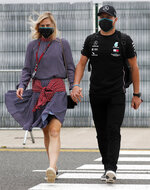 Mercedes driver Valtteri Bottas of Finland, right, and his girlfriend Tiffany Cromwell arrive at the paddocks for preparations before the 70th Anniversary Formula One Grand Prix at the Silverstone circuit, Silverstone, England, Thursday, Aug. 6, 2020.(AP Photo/Frank Augstein)