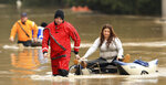 Anna Gaffney is pulled to shore by Jason Clopton of the Russian River Fire District swift water rescue team in Guerneville, Calif., Wednesday, Feb. 27, 2019. Gaffney and a friend were trying to get belongings when they were pulled precariously into the Russian River current. In the background is Mark Haas, also with the department. (Kent Porter/The Press Democrat via AP)