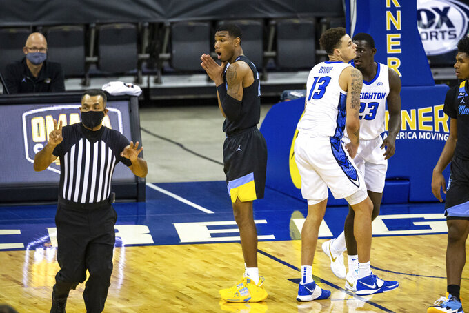 Marquette forward Jamal Cain (23) fouls Creighton forward Christian Bishop (13) in the second half during an NCAA basketball game on Monday, Dec. 14, 2020, in Omaha, Neb. (AP Photo/John Peterson)