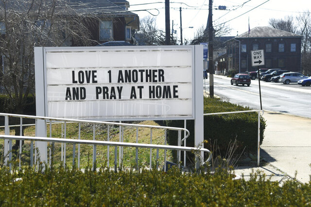 Sign asking to love one another and pray at home in front of St. James Episcopal Church on Dock Street in Schuylkill Haven, Pa., on Sunday, March 22, 2020. Due to the coronavirus pandemic, people are asked to pray at home. (Jacqueline Dormer/The Republican-Herald via AP)