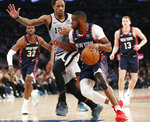 San Antonio Spurs guard DeMar DeRozan (10) defends New York Knicks guard Emmanuel Mudiay (1) who drives to the basket as Knicks forwards Noah Vonleh (32) and Henry Ellenson (13) watch from the floor during the first half of an NBA basketball game in New York, Sunday, Feb. 24, 2019. (AP Photo/Kathy Willens)
