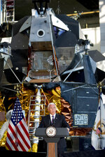 FILE - In this July 16, 2019 file photo, a lunar module, the same type that landed on the moon for Apollo 11, is displayed behind Vice President Mike Pence as he speaks before the unveiling of Neil Armstrong's Apollo 11 spacesuit at the Smithsonian's National Air and Space Museum on the National Mall in Washington. The White House wants U.S. astronauts on the moon by 2024, a scant five years from now. The moon will serve as a critical proving ground, the thinking goes, for the real prize of sending astronauts to Mars. (AP Photo/Andrew Harnik, File)