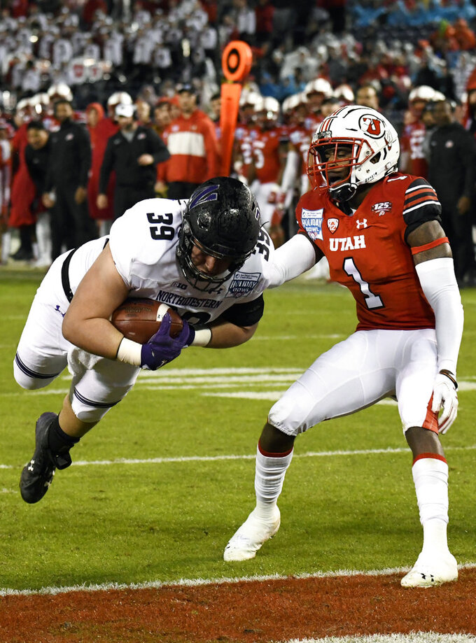 Northwestern offensive lineman Trey Klock (39) dives past Utah defensive back Jaylon Johnson (1) for a touchdown during the second half of the Holiday Bowl NCAA college football game against Utah, Monday, Dec. 31, 2018, in San Diego. (AP Photo/Denis Poroy)