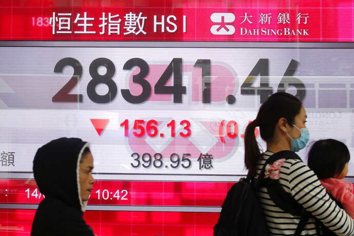 People walk past an electronic board showing Hong Kong share index outside a bank in Hong Kong, Thursday, Feb. 14, 2019. Asian stocks were mostly lower on Thursday as China and the U.S. kicked off two days of trade negotiations in Beijing. (AP Photo/Kin Cheung)