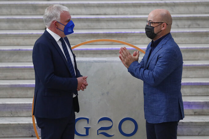 German undersecretary of environment Jochen Flasbarth is welcomed by Italian Minister for Ecological Transition Roberto Cingolani as he arrives at Palazzo Reale in Naples, Italy, Thursday, July 22, 2021, to take part in a G20 meeting on environment, climate and energy. (AP Photo/Salvatore Laporta)