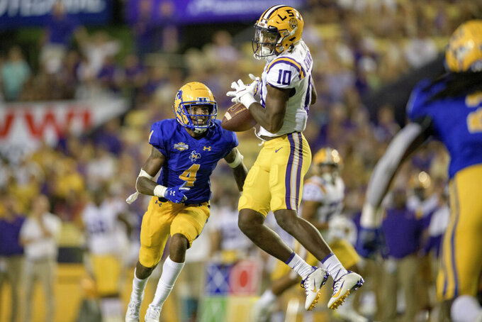 LSU wide receiver Jaray Jenkins (10) drops a pass next to McNeese State cornerback Corione Harris (4) during the first half of an NCAA college football game in Baton Rouge, La., Saturday, Sept. 11, 2021. (AP Photo/Matthew Hinton)