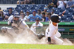 Pittsburgh Pirates' Hoy Park, right, is safe sliding past Milwaukee Brewers catcher Manny Pina, scoring from third on a ground ball to first by Colin Moran, in the third inning of the first baseball game of a split doubleheader Saturday, Aug. 14, 2021, in Pittsburgh. (AP Photo/Keith Srakocic)