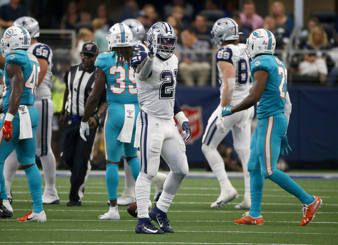 Dallas Cowboys running back Ezekiel Elliott (21) signals first down after carrying the ball against the Miami Dolphins in the second half of an NFL football game in Arlington, Texas, Sunday, Sept. 22, 2019. (AP Photo/Ron Jenkins)