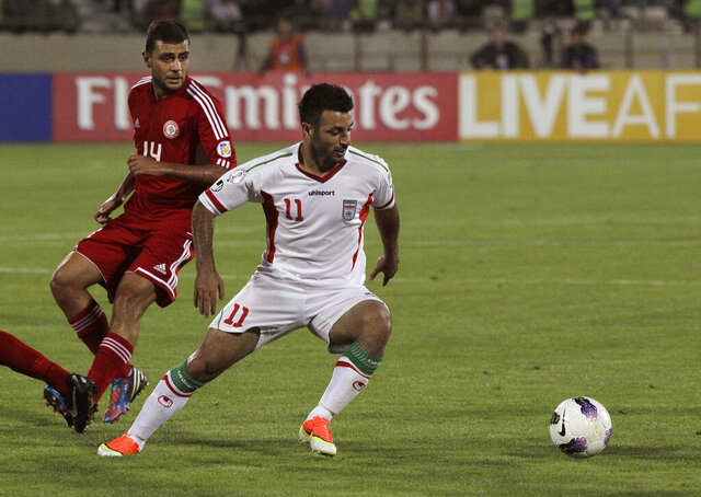 FILE - This Tuesday, June 11, 2013 file photo, Iran's Gholam Reza Rezaei, foreground, plays the ball, as he is followed by Mohamad Atwi, of Lebanon, in their Asian qualifiers soccer match for 2014 World Cup, at the Azadi (Freedom) stadium in Tehran, Iran.  Atwi died Friday, Sept. 18, 2020, nearly a month after he was hit by a stray bullet in his head in Beirut, state-run National news agency reported. Atwi had been in intensive care unit since a stray bullet got stuck in his head on Aug. 21. (AP Photo/Vahid Salemi, File)