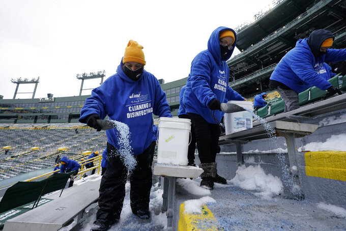 Workers spread salt in the seating area of Lambeau Field before the NFC championship NFL football game between the Tampa Bay Buccaneers and Green Bay Packers in Green Bay, Wis., Sunday, Jan. 24, 2021. (AP Photo/Morry Gash)