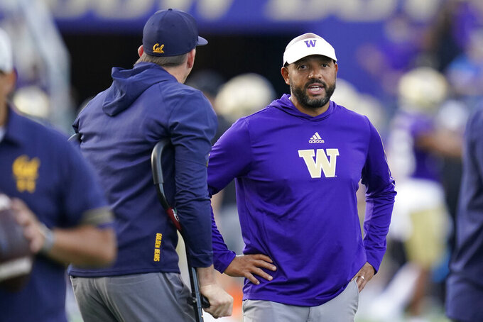 Washington head coach Jimmy Lake, right, talks with California head coach Justin Wilcox, left, before an NCAA college football game, Saturday, Sept. 25, 2021, in Seattle. (AP Photo/Elaine Thompson)