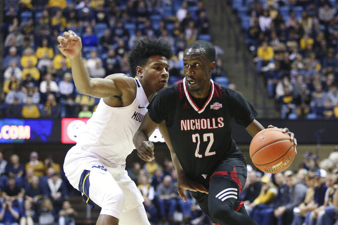 Nicholls State guard Dexter McClanahan (22) is defended by West Virginia guard Miles McBride (4) as he drives it up court during the first half of an NCAA college basketball game Saturday, Dec. 14, 2019, in Morgantown, W.Va. (AP Photo/Kathleen Batten)