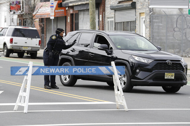A police officer talks to a motorist at an intersection on the border between Irvington and Newark, N.J., Friday, April 3, 2020. The police officers were reminding pedestrians and the occasional motorist to avoid unnecessary travel and practice social distancing. (AP Photo/Seth Wenig)