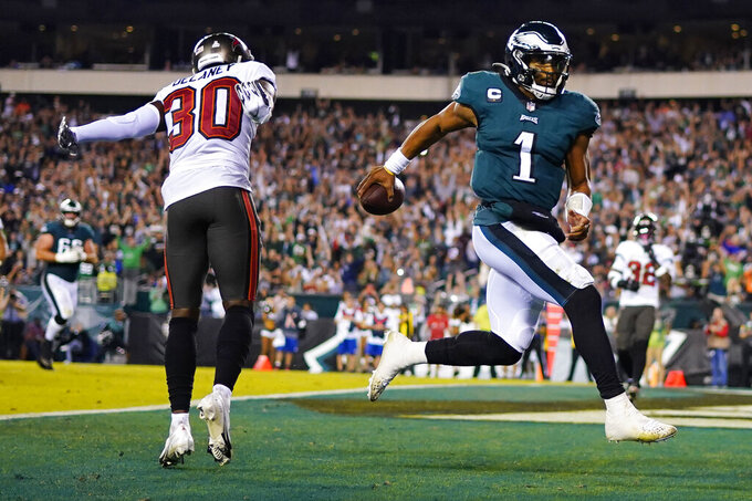 Philadelphia Eagles quarterback Jalen Hurts (1) scores a touchdown in front of Tampa Bay Buccaneers defensive back Dee Delaney (30) during the second half of an NFL football game Thursday, Oct. 14, 2021, in Philadelphia. (AP Photo/Matt Slocum)