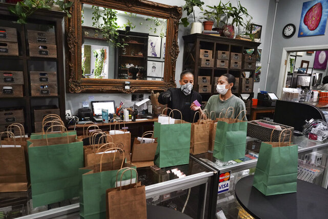 In this Thursday, April 16, 2020, photo, wearing a protective mask and gloves, budtenders prepare orders for customers to pick-up at The Higher Path cannabis dispensary in the Sherman Oaks section of Los Angeles. Monday is April 20, or 4/20. That's the code for marijuana's high holiday, which is usually marked with outdoor festivals and communal smoking sessions. But this year, stay-at-home orders have moved the party online as the marijuana market braces for an economic blow from the coronavirus crisis. (AP Photo/Richard Vogel)