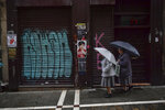 Two nuns shelter under umbrellas while walking past a basque nationalist campaign cartel, center, the day after the general election, in Pamplona, northern Spain, Monday, Nov. 11, 2019. Spain looked set Monday to face political uncertainty for many more months after the country's fourth elections in as many years further complicated an already messy political situation.  (AP Photo/Alvaro Barrientos)