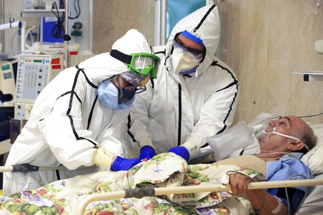 FILE - In this Oct. 14, 2020, photo provided by the Iranian Health Ministry, medics tend to a COVID-19 patient at a hospital in Tehran, Iran. Iranian media reported on Monday, Dec. 28 that an unidentified group of U.S.-based philanthropists plans to send 150,000 doses of the Pfizer vaccine to Iran in the coming weeks, in a step that could bring the hardest-hit country in the Middle East closer to inoculating its citizens against the coronavirus. (Akbar Badrkhani/Iranian Health Ministry via AP, File)
