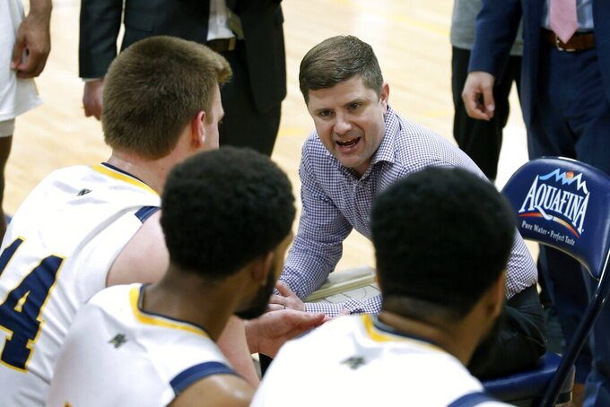 In this Thursday, Feb. 27, 2020 photo, Merrimack College head coach Joe Gallo directs his team during a timeout in the second half of an NCAA college basketball game against Central Connecticut in North Andover, Mass. The Warriors have been one of the biggest surprises in college basketball, winning more games than any other first-year Division I program in history. (AP Photo/Mary Schwalm)
