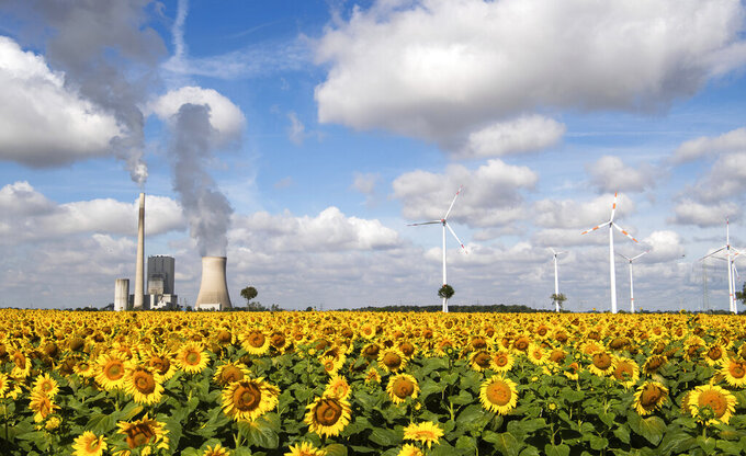 A field of sunflowers is within sight of the Mehrum coal-fired power station, wind turbines and high-voltage lines in Mehrum, Germany, Monday, Aug. 3, 2020. In the energy turnaround, energy sources such as coal are to be replaced by more environmentally friendly energy sources from the sun and wind. The phase-out of coal is planned by 2038 at the latest. (Julian Stratenschulte/dpa via AP)