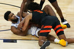 UCLA's Cody Riley, left, and Oregon State's Ethan Thompson (5) scramble for the ball during the second half of an NCAA college basketball game in the quarterfinal round of the Pac-12 men's tournament Thursday, March 11, 2021, in Las Vegas. (AP Photo/John Locher)