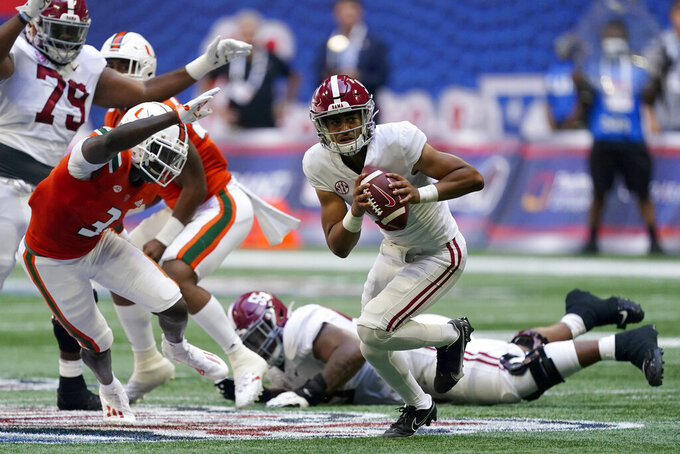 Alabama quarterback Bryce Young (9) scrambles away from Miami safety Gilbert Frierson (3) before throwing a touchdown pass during the first half of an NCAA college football game Saturday, Sept. 4, 2021, in Atlanta. (AP Photo/John Bazemore)