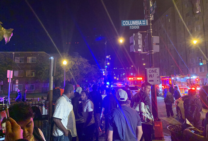 In this photo provided by Peter Sacco, a crowd gathers at a cordoned-off intersection near a shooting Thursday, Sept. 19, 2019, in a Washington D.C. neighborhood. Police say one man was killed and five other adults were wounded in a shooting in the courtyard of an apartment complex near Columbia Heights Metro Station in the nation's capital. (Peter Sacco via AP)