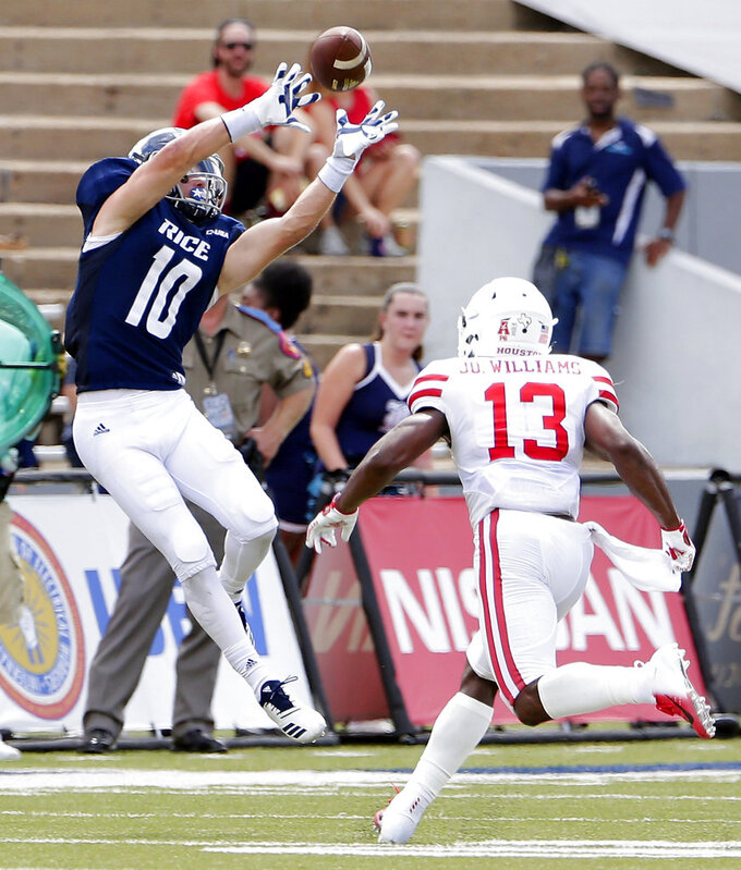 Rice wide receiver Austin Trammell (10) makes the reception over Houston cornerback Joeal Williams (13) during the first half of a NCAA college football game Saturday, Sep. 1, 2018, in Houston. (AP Photo/Michael Wyke)