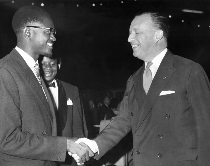 FILE - In this July 4, 1960 file photo, first Prime Minister of the Congo Patrice Lumumba, left, shakes hands with Belgium's ambassador Jean van den Bosch, right, at a farewell dinner for press representatives who covered the Congo independence ceremonies, in Leopoldville, the capital before it was later renamed in 1966 to Kinshasa, in Congo. On Tuesday, June 30, 2020 Congo is marking the 60th anniversary of achieving independence from the colonial rule of Belgium. (AP Photo, File)