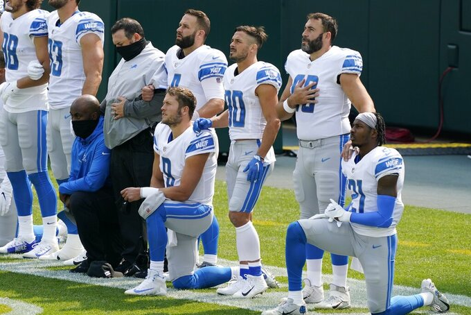 Detroit Lions' Matthew Stafford and Tracy Walker take a knee during the national anthem before an NFL football game against the Green Bay Packers Sunday, Sept. 20, 2020, in Green Bay, Wis. (AP Photo/Morry Gash)