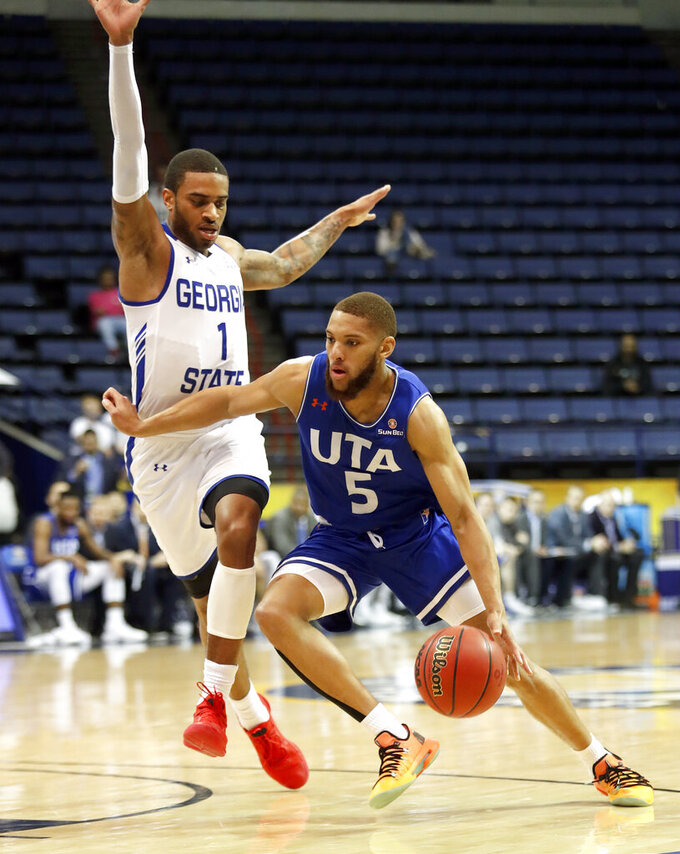 Texas-Arlington guard Edric Dennis (5) drives past Georgia State guard Damon Wilson (1) during the first half of the NCAA college basketball championship game of the Sun Belt Conference men's tournament in in New Orleans, Sunday, March 17, 2019. (AP Photo/Tyler Kaufman)