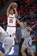 Utah guard Alfonso Plummer (25) shoots as UC Davis guard Ezra Manjon defends during the second half during an NCAA college basketball game Friday, Nov. 29, 2019, in Salt Lake City. (AP Photo/Rick Bowmer)