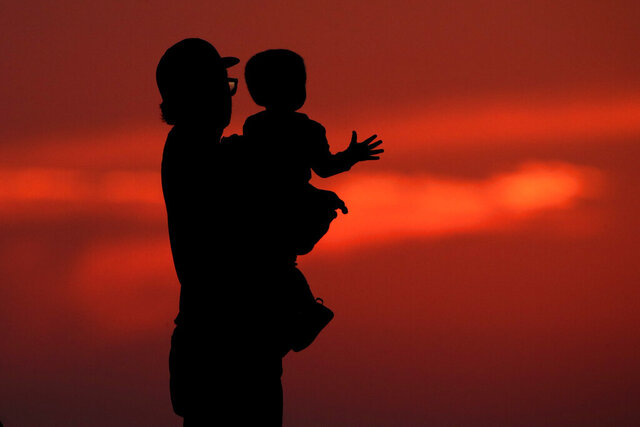 FILE - In this June 26, 2020 file photo, a man and his son are silhouetted against the sky as they watch the sunset from a park in Kansas City, Mo. Health experts once thought 2020 might be the worst year yet for a rare paralyzing disease that has been hitting U.S. children for the past decade.  But they now say the coronavirus pandemic could disrupt the pattern for the mysterious illnesses, which spike every other year starting in late summer. (AP Photo/Charlie Riedel, File)