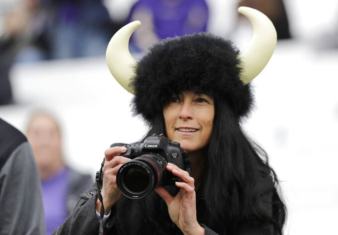 A Colorado fan wears a buffalo hat as she takes photos before an NCAA college football game against Washington, Saturday, Oct. 20, 2018, in Seattle. (AP Photo/Ted S. Warren)