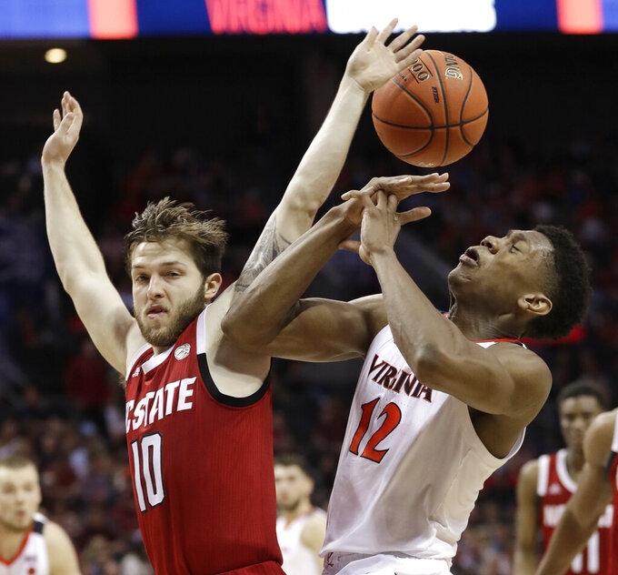 Virginia's De'Andre Hunter (12) is fouled by North Carolina State's Braxton Beverly (10) during the second half of an NCAA college basketball game in the Atlantic Coast Conference tournament in Charlotte, N.C., Thursday, March 14, 2019. (AP Photo/Nell Redmond)