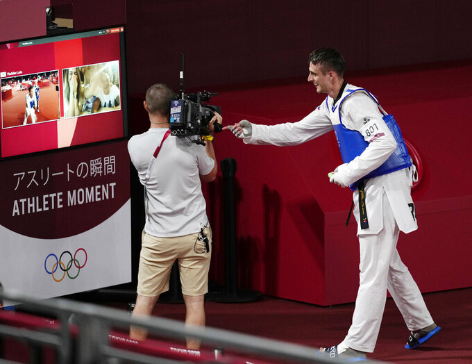 Vladislav Larin of the Russian Olympic Committee celebrates with his family via a video link after winning a gold medal for taekwondo men's 80kg match at the 2020 Summer Olympics, Tuesday, July 27, 2021, in Tokyo, Japan. (AP Photo/Themba Hadebe)