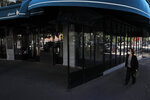 A woman walks past an empty terrace of a restaurant in Paris, Thursday, May 28, 2020. France is reopening its restaurants, bars and cafes starting next week as the country eases most restrictions amid the coronavirus crisis. Edouard Philippe defended the gradual lifting of lockdown up to now, saying the strategy was meant to avoid provoking a second wave. (AP Photo/Christophe Ena)