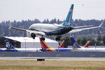 A Boeing 737 MAX jet heads to a landing and past grounded 737 MAX jets behind at Boeing Field following a test flight Monday, June 29, 2020, in Seattle. The jet took off from Boeing Field earlier in the day, the start of three days of re-certification test flights that mark a step toward returning the aircraft to passenger service. The Federal Aviation Administration test flights over the next three days will evaluate Boeing's proposed changes to the automated flight control system on the MAX, a system that activated erroneously on two flights that crashed, killing 346 people. (AP Photo/Elaine Thompson)