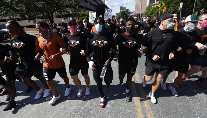 Members of the Austin police department march with members of the University of Texas football team to the State Capitol in Austin, Texas, Thursday, June 4, 2020, during a protest over the death of George Floyd, who died May 25 after being restrained by police in Minneapolis. (AP Photo/Eric Gay)