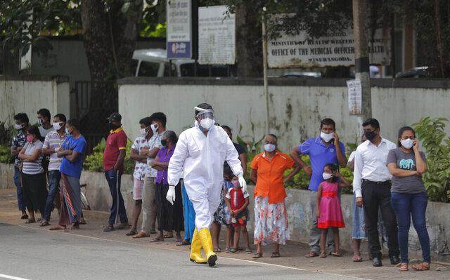 Sri Lankans wait to give swab samples to test for COVID-19 outside a hospital as a health official walks past in Minuwangoda, Sri Lanka, Tuesday, Oct. 6, 2020. (AP Photo/Eranga Jayawardena)